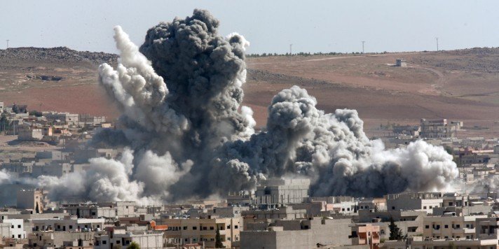 Thick smoke from an airstrike by the US-led coalition rises in Kobani, Syria, as seen from a hilltop on the outskirts of Suruc, at the Turkey-Syria border, Wednesday, Oct. 22, 2014. Kobani, also known as Ayn Arab, and its surrounding areas, has been under assault by extremists of the Islamic State group since mid-September and is being defended by Kurdish fighters. (AP Photo/Lefteris Pitarakis)